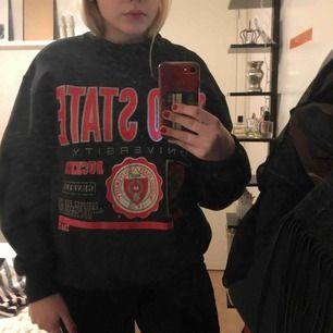 En svart tjockare långärmad tröja med röd/grå text. Köpt second hand. Storlek L som funkar som M perfekt!