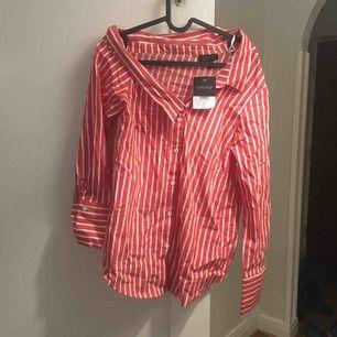 Osymmetrisk randig skjorta från Topshop. Aldrig använd. Frakt tillkommer.