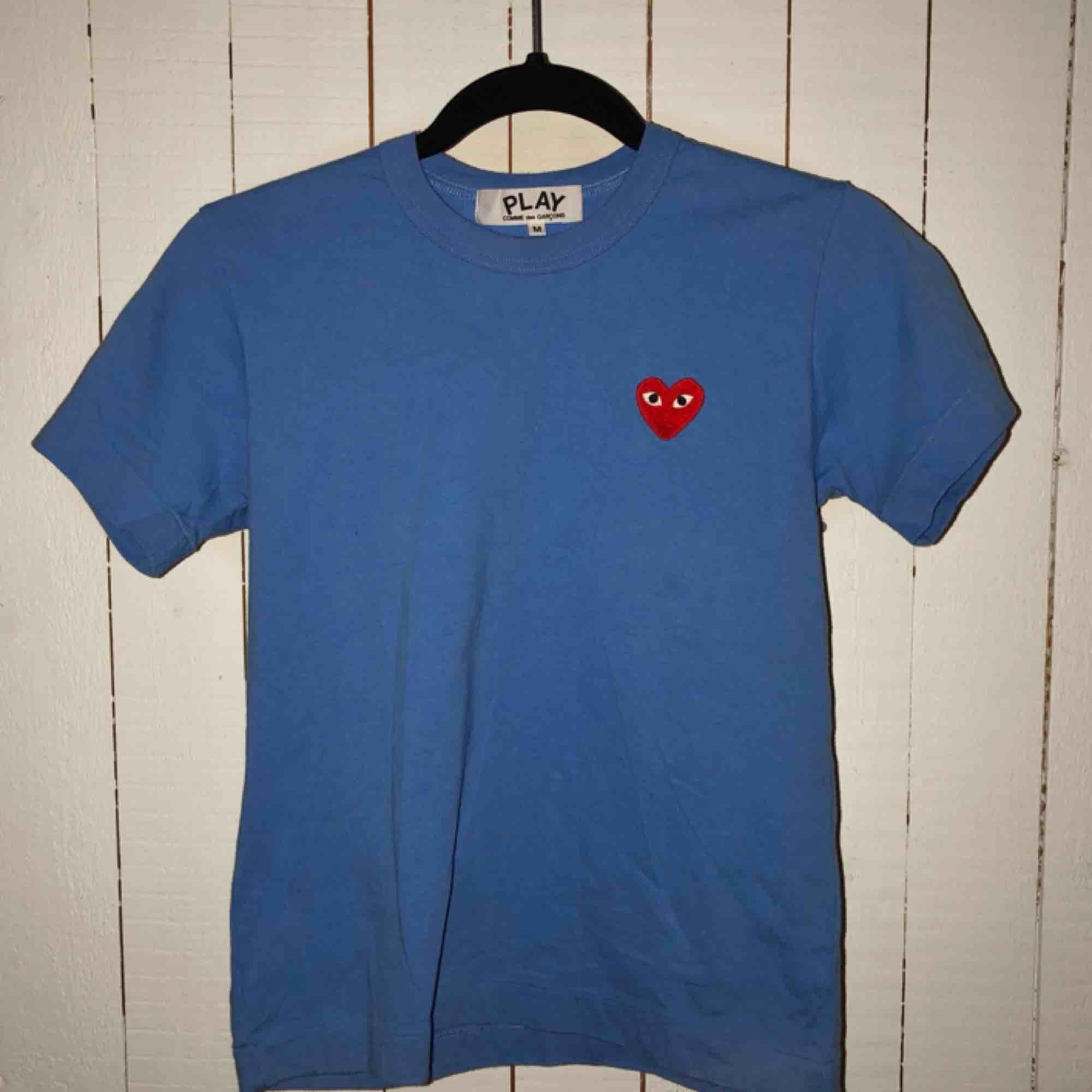 En sprillans Comme des garcons tshirt, helt äkta! Använde den två gånger - jättebra skick, tvättad 1 gång. Priset kan diskuteras.  Nypris: ca 1000kr Köparen står för eventuell frakt, jag kan annars mötas upp i Helsingborgsområdet!. T-shirts.