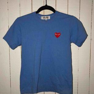 En sprillans Comme des garcons tshirt, helt äkta! Använde den två gånger - jättebra skick, tvättad 1 gång. Priset kan diskuteras.  Nypris: ca 1000kr Köparen står för eventuell frakt, jag kan annars mötas upp i Helsingborgsområdet!
