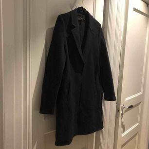 Mörkblå tunnare kappa i klassisk modell, perfekt till vardags.