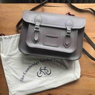 """13 inch väska från """"The Cambridge satchel company"""". Köpt för 2000 kr och har blivit använd ungefär 2 gånger. Mörkbrun i äkta läder och silverspännen. Frakt ingår. Pris kan diskuteras :)"""