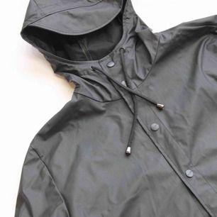 En lång svart regnkappa från Rains, använd 3-4 gånger. I väldigt fint skick. Frakten kostar 50kr. Originalpris 900kr