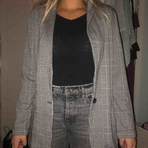 Grå rutig blazer/kavaj från H&M. Aldrig använd. Storlek 40 men är som en storlek 38. Två fickor och knapp där framme