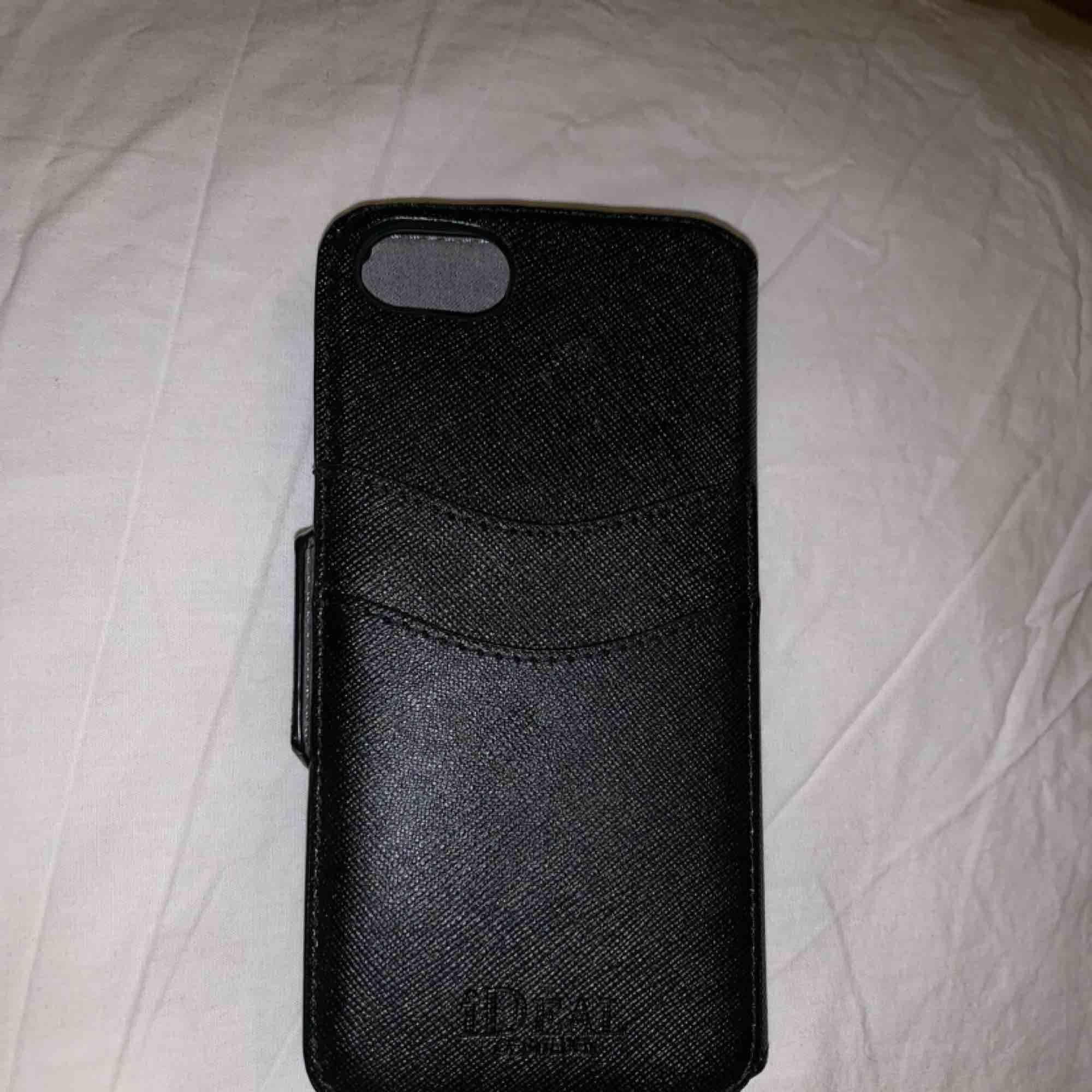 Helt oanvänd plånboks fodral, med avtagbart skall från Ideal of sweden Passar IPhone 7 och 8  Plats till två kort på baksidan  Orginalpris: 399 ( köpt på ur & Penn) Mitt pris: 250  frakten ingår, snabb affär 200. Accessoarer.