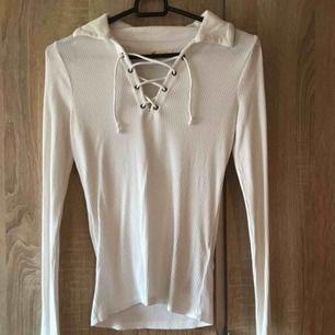 En vit snörad tröja ifrån Hollister i strl S. Ignorera att jag har en grå bh på mig under. Fint skick. 60kr  Köpare står för ev. frakt