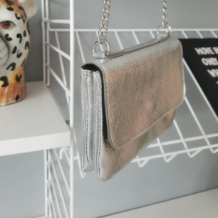 Silvrig handväska i fake läder från Monki. Aldrig använd. Super fin med silvriga kedjor på axelremmen.  Köparen står för frakten.