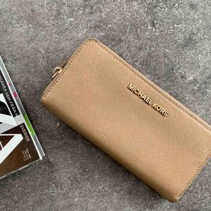 En äkta Michael kors plånbok. Säljer billigt då den är använd ganska mycket, men absolut i fint skick.