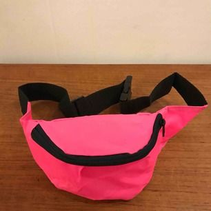 Magväska i enkel nylon modell från 90-talet.  Har ett litet parti med denna rosa neon färg och även svart och mörkblå.
