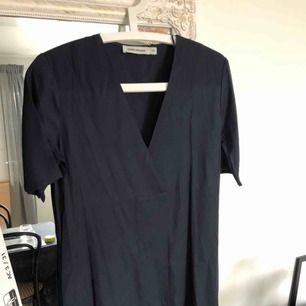 Oanvänd klänning från Carin Wester. Mörkblå med stilfull v-ringning, rak i modellen. Lite skrynklig på bilden men i övrigt felfri! Priset kan diskuteras vid snabb affär.