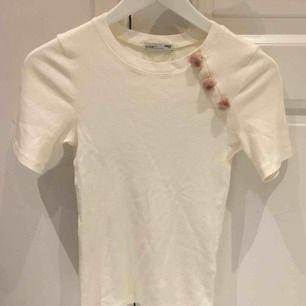 En crémefärgad ribbad t-shirt med puderrosa tussar på. Lite längre ärmar och i modellen. Aldrig använd så i bra skick!💖