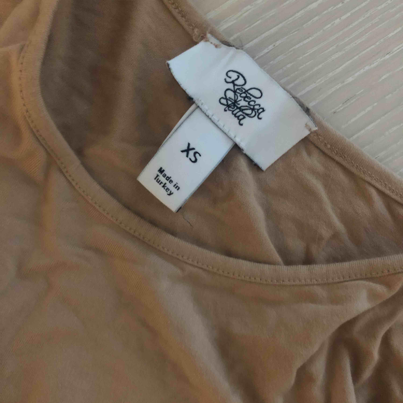 Beige/nude body från Rebecca Stella. Endast använd på bild. En knapp saknas i knäppet mellan benen (se bild) . Toppar.