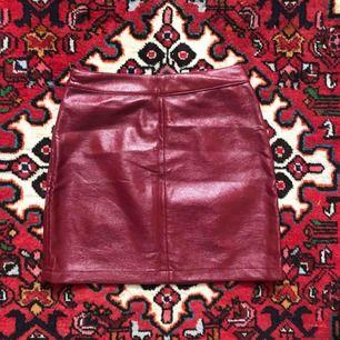 Kjol i röd lack/konstläder.  Passform: tajt.  Köparen står för frakt, kan även mötas upp!