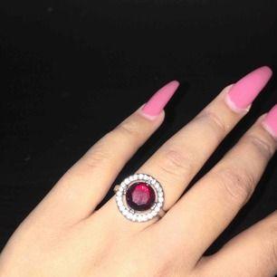 Ring med en röd pärla och vita diamanter på sidan. Oanvänd