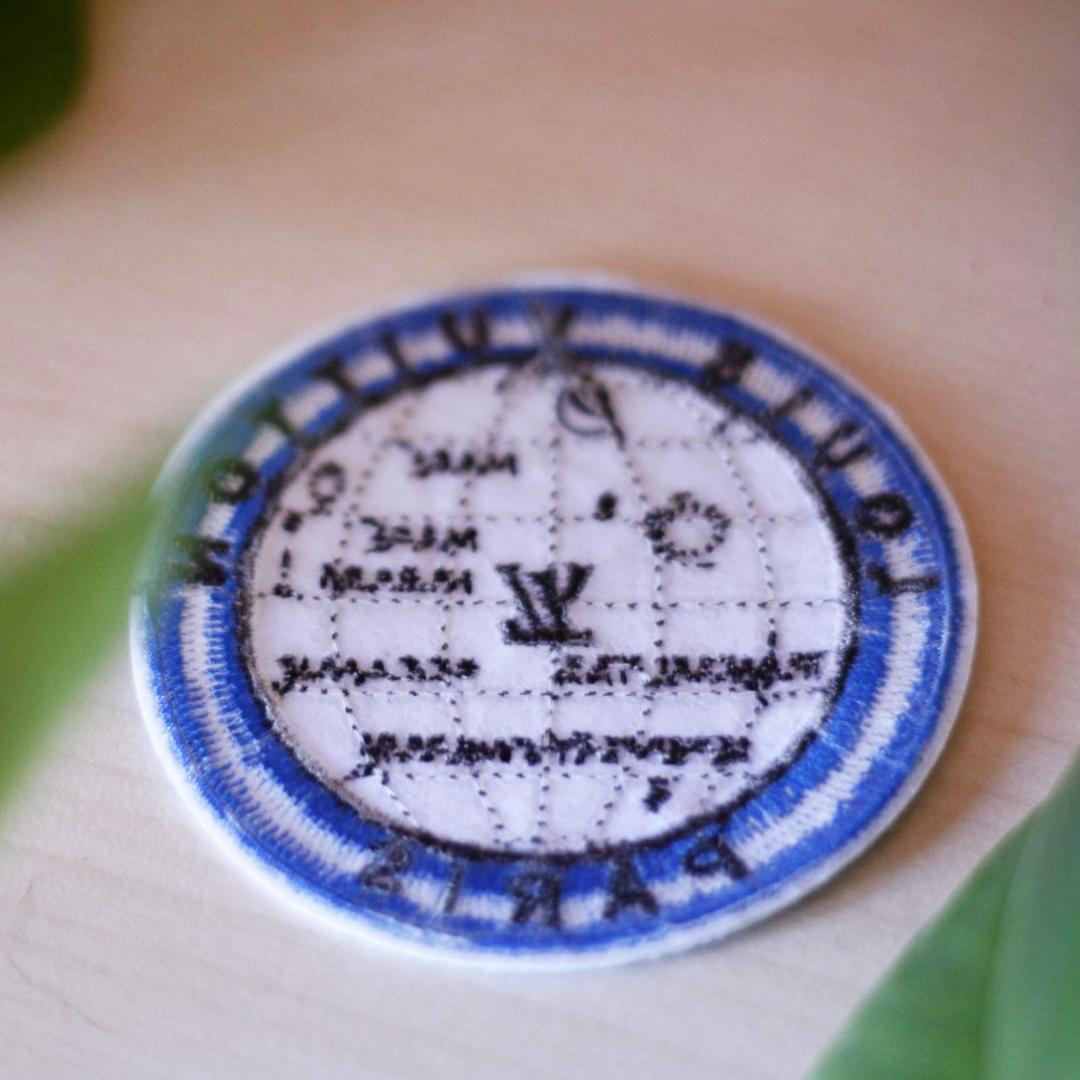 Tygmärke av en jordglob och med texten Louis Vuitton Paris inbroderat. 39kr inkl frakt!! . Övrigt.