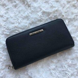 Svart plånbok från Björn Borg. I bra skick. Plats för 10 kort. Har även ett sedelfack och en myntficka med dragkedja. En iPhone 6/6s rymmer också väldigt bra i plånboken. Frakt inkl. i priset.