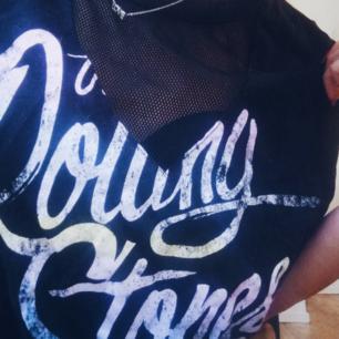 Äkta merchandise the Rolling Stones t-shirt utan ärmar med v-ringat nättyg, i svart med detaljer i pastell. I fint skick och frakt tillkommer vid köp 🖤