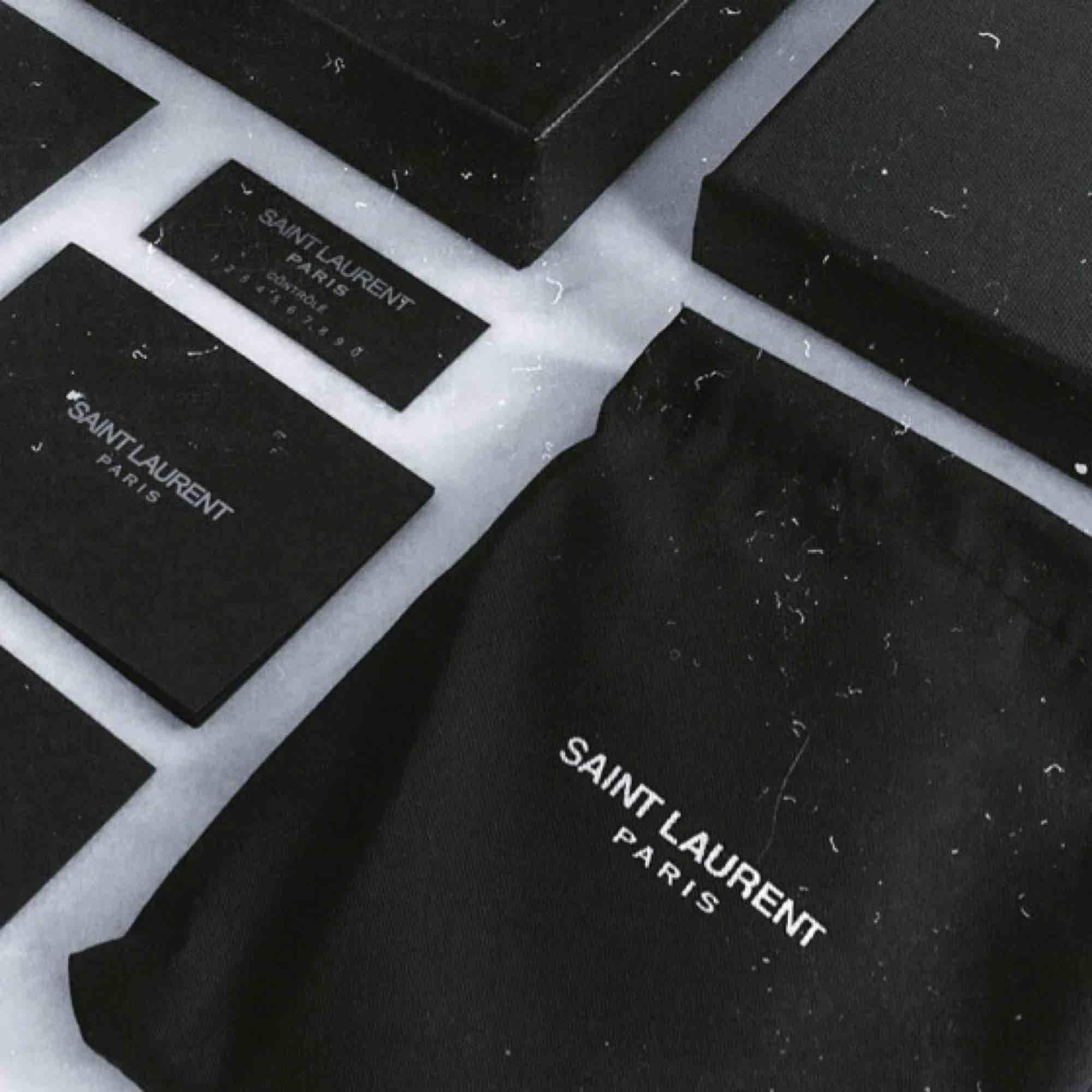 YSL / Saint Laurent plånbok/korthållare.  5 fickor för kort och ett fack med dragkedja för mynt/sedlar.  Riktigt bra kvalité, oanvänd och kommer med box, dust bag och Saint Laurent kort. I mitt pris så bjuder jag på frakten! :). Accessoarer.