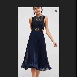 Väldigt fin midiklänning, passar perfekt för bröllop och fest. Mörkblå med svarta virkade detaljer. Knäppning med dragkedja. Oanvänd med tagg kvar.  Nypris: 800kr *Obs! Första bilden är från hemsidan.