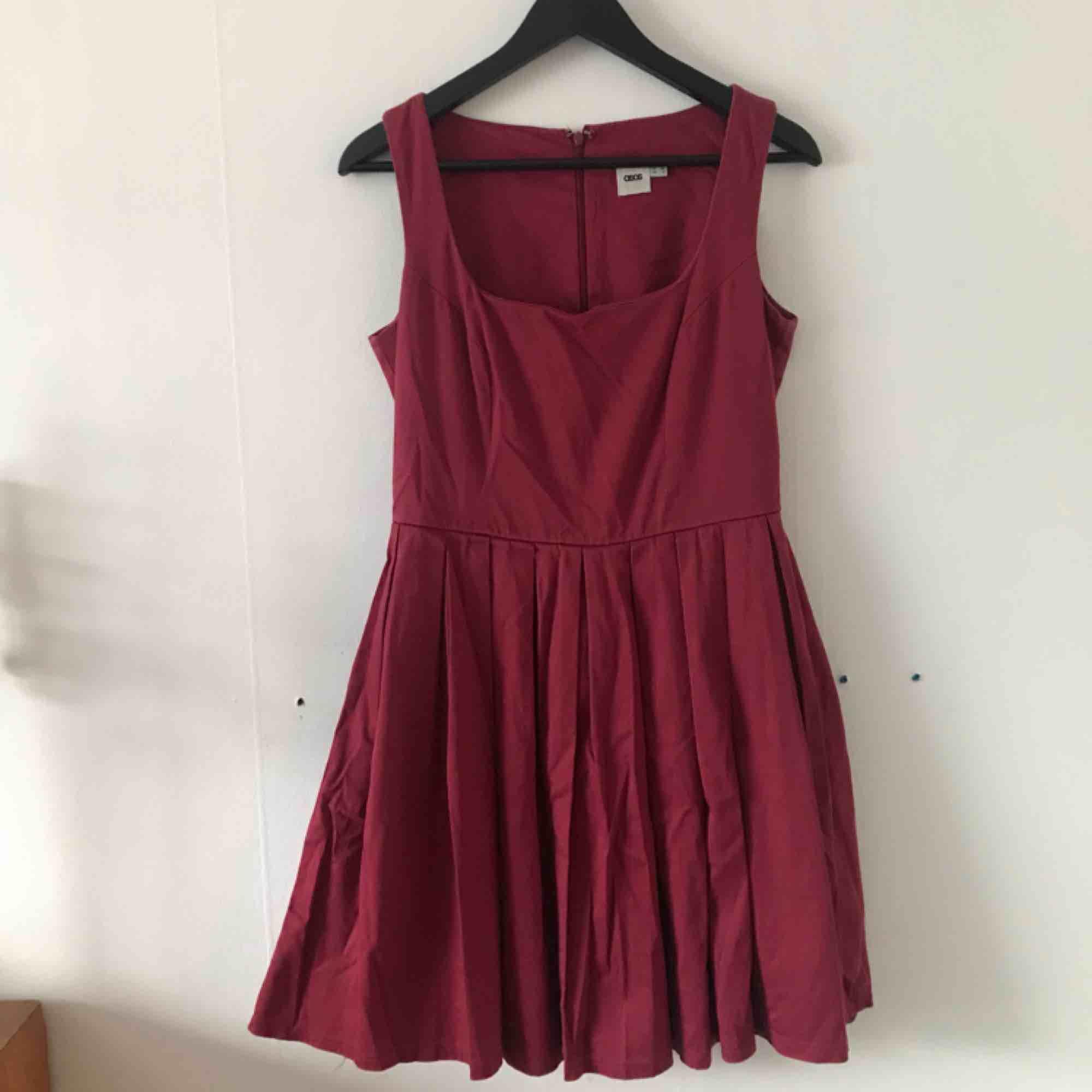 Mörkröd klänning från ASOS. I bra skick, dock kärvar dragkedjan lite i mitten av ryggen. Använd endast en handfull gånger. Kan mötas i Göteborg eller skicka med post (köparen betalar frakt). Klänningar.