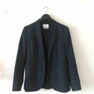 Mörkblå kavaj från Filippa K. Modellen heter Gracie Linen Mix Jacket och köptes för ca 3000. Insidan av ärmarna är vita och väldigt snygga uppvikta. Använd men i gott skick. Kan mötas i Göteborg eller skicka med post (köparen betalar frakt)