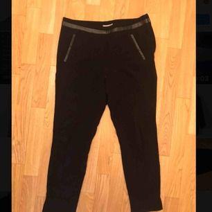 Svarta kostymbyxor med (fake)skinndetaljer från H&M. Knappt använda. Kan mötas i Göteborg eller skicka med post (köparen betalar frakt)