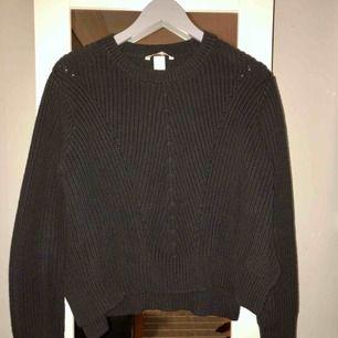 Stickad tröja från H&M, normal i passform. Färgen är mörkgrå/svart. Ser ny och fin ut! Fri frakt!