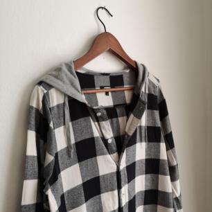 Svart/grå/vit-rutig skjorta med grå luva.