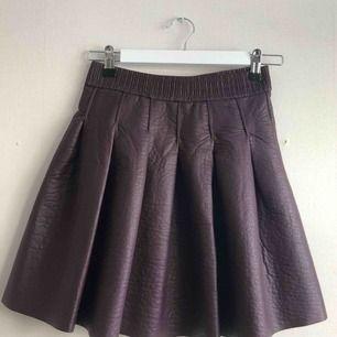 Supersnygg burgundy kjol i fake läder/skinn med en dragkedja där bak från HM. Andvänd bara 2-3 gånger,Kommer ej till användning längre! Jättefint skick✨frakt tillkommer😊