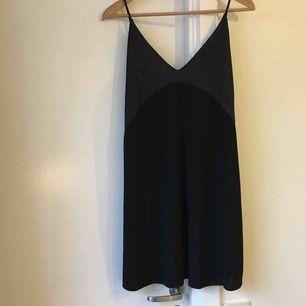 Svart kort klänning i polyester med vringad glitterkant. Fint skick!