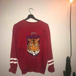 """röd """"tiger"""" sweatshirt med hål på. fraktkostnad tillkommer!"""