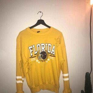 """gul """"collage"""" sweatshirt. Har en fläck (se bild 2), fläcken syns inte jätteväl.  fraktkostnad till kommer!"""