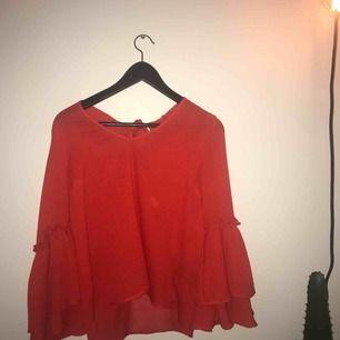 röd blus med rosetter på ryggen! jättefin men för liten för mig :/. fraktkostnad tillkommer!