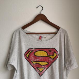Oversize tshirt med slitet utseende. Ljusgrå med supermanmärket (: