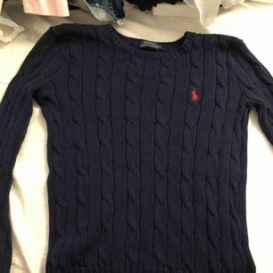 Marinblå kabelstickad tröja med rött märke i storlek S. Använd fåtal gånger.