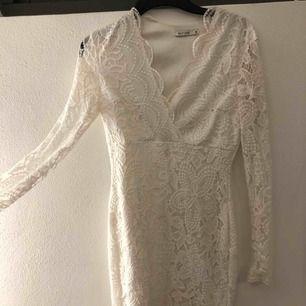 Vit spetsklänning med V-ringning