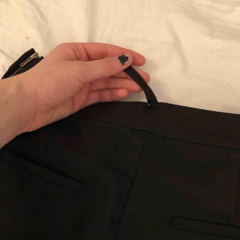 Vanliga svarta kostymbyxor, väldigt snygga med en dragkedja på sidan av byxorna. Dock har en av öglorna gått isönder men jag personligen brukar inte ha skärp i kostymbyxor men skulle man önska de funkar det endå.. Kostymer.