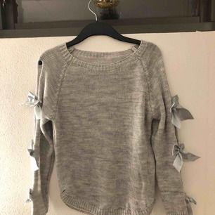 Grå stickad tröja med rosetter på armarna. Står ingen storlek men skulle säga att den är en S/M. Aldrig använt men prislapp finns inte kvar.
