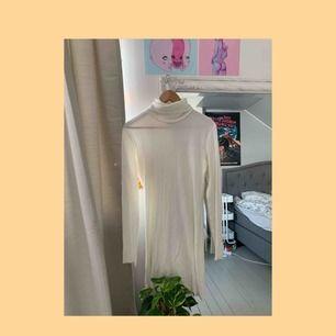 Snygg vit ribbad klänning med polokrage, man kan klä både ner och upp den. Den är inte genomskinlig på!