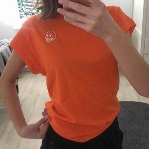 En orange t-shirt med cheap monday märket på sidan av bröstet.Säljs på grund av att den aldrig kom till användning.Köparen står för frakten!❣️ Nypris:200 Skicka om nån vill ha blid på hur den ser ut på💋