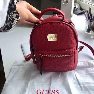 Splitterny ryggsäck från Guess, går även att bära i handen. Superfin röd färg och aldrig använd, därav är innehållet kvar. Påse medföljer. Inköpt för ca 1300kr