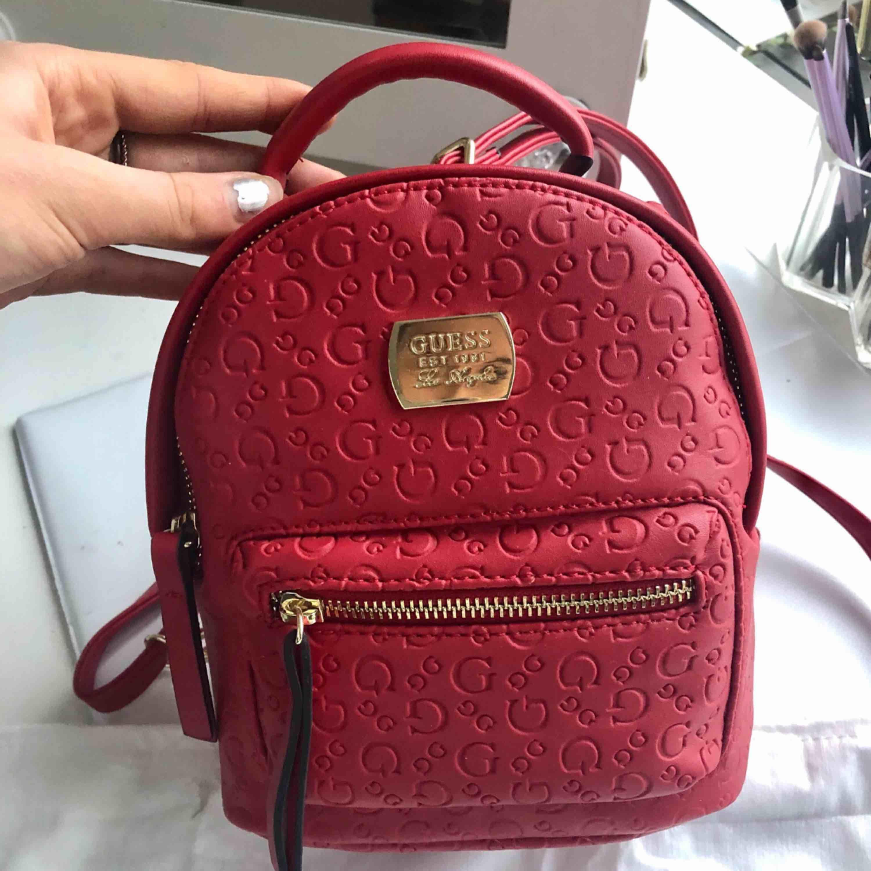 Splitterny ryggsäck från Guess, går även att bära i handen. Superfin röd färg och aldrig använd, därav är innehållet kvar. Påse medföljer. Inköpt för ca 1300kr . Väskor.