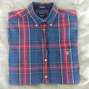 Gant klassisk flerfärgad skjorta i stl M herr. Modellen är en Indigo Oxford i Classic fit med button down-krage. Gjord i 100% bomull. I begagnat skick, använd en del men superbra skick och håller länge till. Frakt 55 kr.