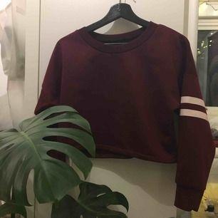 En jättecool croppad, lite tjockare, mörkrödtröja! Den har två streck på båda ärmarna! Passar xs/s/m! Älskade denna tröjan men den har knte kommit till användning!🌸 köparen står för frakt: 36kr