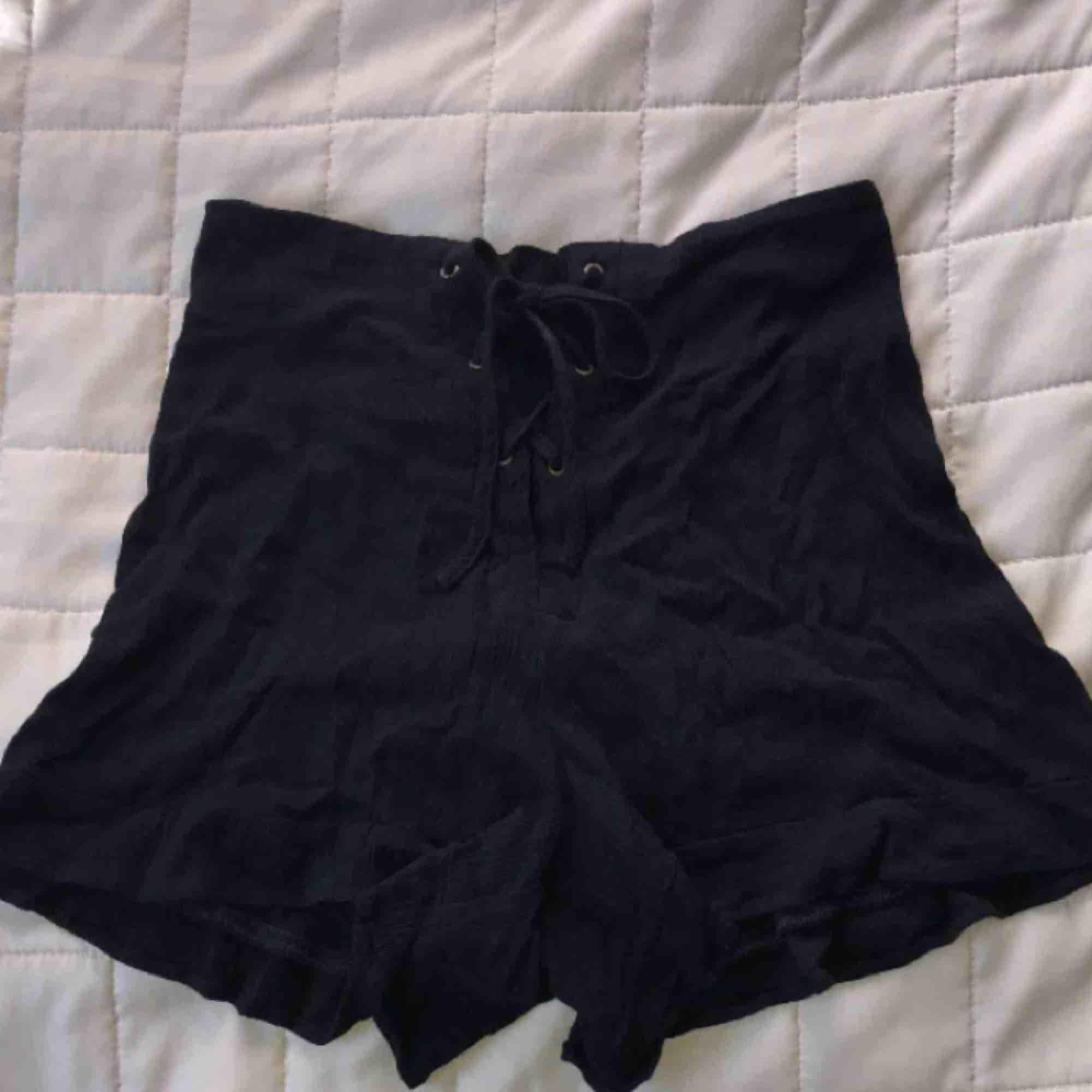 Högmidjade shorts. Midjan kan justeras å anpassas (snörning). Shorts.