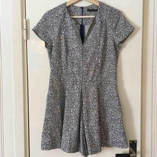 """Söt byxdress från Zara, inköpt för flera år sedan men knappt använd. Blå-vitt blommönster och en ficka på var sida av """"byxdelen"""".  Dragkedja längs ryggen."""