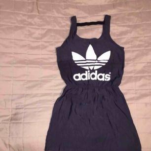Oanvänd Adidas Originals klänning med prislappen kvar! Klänningenr har ett band på baksida rygg/nacke (se sista bild) och resår runt midjan. 100% polyester. Storlek 30 vilket motsvarar XX-SMALL / X-SMALL