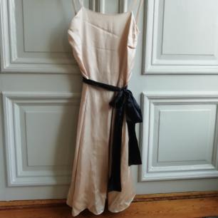 Beige sidenklänning med svart skärp. Knappt använd med ej tvättad. Finns någon liten fläck som nog går bort vid tvätt. Nypris 2000kr.