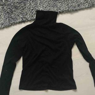Fin långärmad tröja med hög krage och öppen rygg. Aldrig använd.