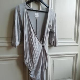 Ljusgrå omlottklänning i skönt material.